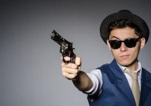 Man wearing sunglasses with gun