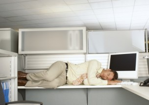 Exhausted businessman sleeping on top of his desk