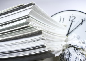 Stack of documents and clock.