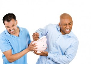 Two angry men fight over piggy bank profit inheritance